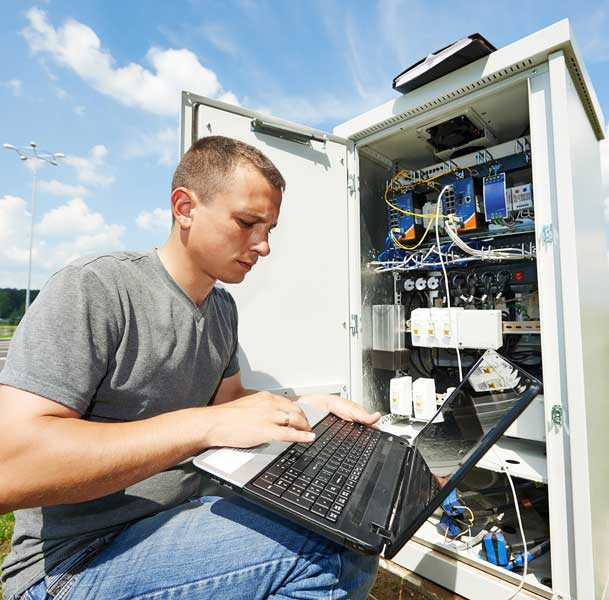 telecommunications engineer working on laptop connected to panel